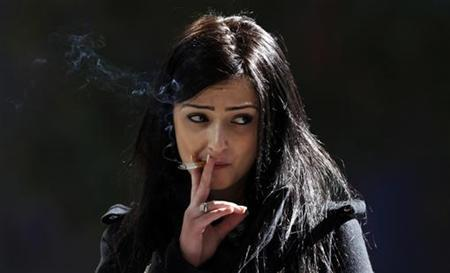A woman smokes a cigarette outside an office building in central Sydney